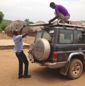 Fambul Tok staff, Rev. Emmanuel, and local villiager unloading tin